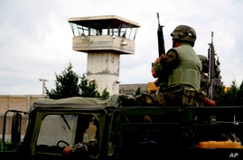 Soldiers patrol outside Cieneguillas state prison in c, Mexico, Saturday, May 16, 2009.  An armed gang freed more than 50…