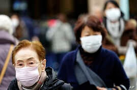 Pedestrians wear protective masks as they walk through a shopping district in Tokyo Thursday, Jan. 16, 2020. Japan's government…