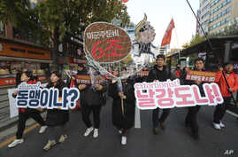 Protesters march to oppose the United States' demand for raising the defense costs for stationing U.S. troops in South Korea,…