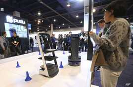 People check out the Pudu delivery robots at the Pudu booth during the CES tech show Wednesday, Jan. 8, 2020, in Las Vegas. (AP…