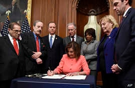 House Speaker Nancy Pelosi of Calif., signs the resolution to transmit the two articles of impeachment against President Donald…