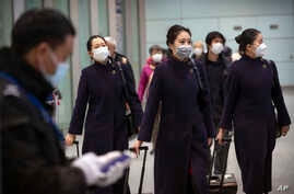 Flight crew members wearing face masks walk through the international arrivals area at Beijing Capital International Airport in…