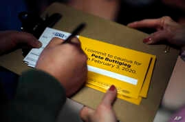 A person signs up to caucus for Democratic presidential candidate former South Bend, Ind., Mayor Pete Buttigieg, following a…