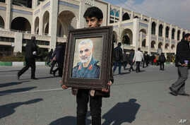 A boy carries a portrait of Iranian Revolutionary Guard Gen. Qassem Soleimani, who was killed in the U.S. airstrike in Iraq,…
