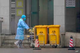 Staff move bio-waste containers past the entrance of the Wuhan Medical Treatment Center, where some infected with a new virus…