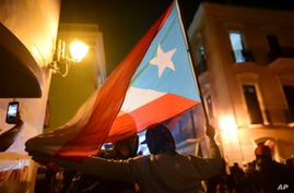 Protesters hold a Puerto Rican flag during a protest in San Juan, Puerto Rico, Thursday, Jan. 23, 2020. Hundreds of people…