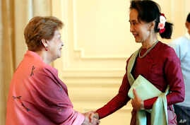 Myanmar's leader Aung San Suu Kyi, right, shakes hands with Philippine diplomat Rosario Manalo, a member of the Independent…
