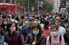 People wear masks on a street in Hong Kong, Friday, Jan. 24, 2020 to celebrate the Lunar New Year which marks the Year of the…