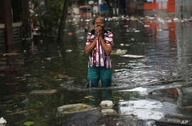 A woman reacts as she wades flood water in Jakarta, Indonesia, Saturday, Jan. 4, 2020. Monsoon rains and rising rivers…