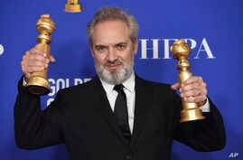 """Sam Mendes poses in the press room with the awards for best director, motion picture and best motion picture drama for """"1917""""…"""