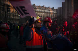 Striking workers are lit by a flare during a demonstration, Thursday, Jan. 16, 2020 in Paris. Protesters are marching in the…