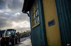 A farmer drives a tractor past an old customs post at the border between with the Republic of Ireland and Pettigo, Northern…