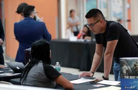 FILE - In this Oct. 1, 2019, file photo, Gabriel Picon, right, talks with a representative from GameStop during a job fair at…