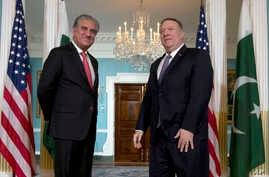 Secretary of State Mike Pompeo stands with Pakistani Foreign Minister Shah Mehmood Qureshi at the Department of State in…
