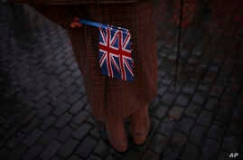 """A man holds Union flags during an event called """"Brussels calling"""" to celebrate the friendship between Belgium and Britain at…"""