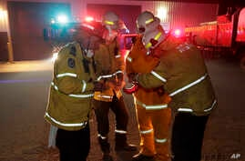 Firefighters at Burragate, Australia, gather outside the firehouse as they discuss a nearby fire threat Friday, Jan. 10, 2020…