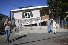 Residents survey damage where a home partially collapsed after an earthquake hit Guanica, Puerto Rico, Monday, Jan. 6, 2020. A…