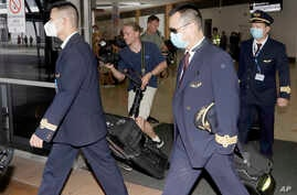 Crew from China Eastern Airlines leave the airport wearing face masks after arriving in Sydney Thursday, Jan. 23, 2020, on a…