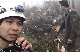 In this image made from video, emergency teams work at the crash site of a military helicopter in the mountains of Yilan, north…