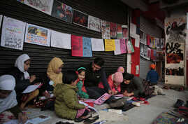 In this Tuesday, Jan. 21, 2020 photo, young girls draw sketches near the protest site in New Delhi's Shaheen Bagh area, India…