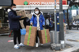 People leave after buying face masks at a pharmacy in Seoul, South Korea, Wednesday, Jan. 29, 2020. Countries began evacuating…