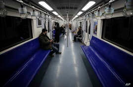 FILE - In this Feb. 17, 2020, file photo, commuters ride in a quiet subway train during the morning rush hour in Beijing. As…