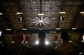FILE - In this Dec. 20, 2019, file photo members of the military attend a ceremony at Andrews Air Force Base, Md. Suicides in…