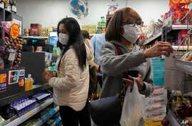 People wear protective face masks as they make purchases from a convenience store in Hong Kong, Monday, Feb, 3, 2020. Hong Kong…