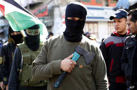 Masked member of Hamas holds an axe on his chest as others wave their national flags during a protest against the Mideast plan…