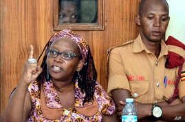 In this photo taken on Monday April 10, 2017, Makerere University researcher Dr Stella Nyanzi, left, gestures in the dock at…