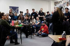 Caucus-goers listen as a supporter of Democratic presidential candidate, former South Bend, Ind., Mayor Pete Buttigieg, right,…