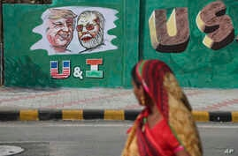 An Indian woman looks at a wall painted with portraits of U.S. President Donald Trump and Indian Prime Minister Narendra Modi…