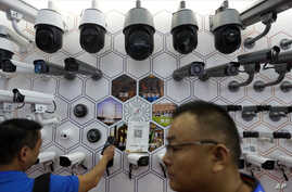 FILE - In this Oct. 29, 2019, file photo visitors look at the surveillance cameras by China's telecoms equipment giant Huawei…
