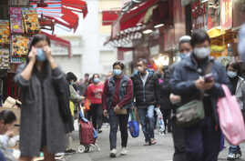 People wearing masks at a market in Hong Kong, Monday, Feb, 3, 2020. China's death toll from a new virus has risen hundreds and…