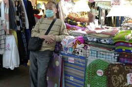 A vendor wears a face mask and waits for customers at a night market in Taipei, Taiwan, Thursday, Feb. 6, 2020. According to…