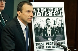 Raymond Duda, FBI Special Agent in Charge in Seattle, speaks as he stands next to a poster that was mailed earlier in the year…