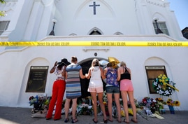 FILE - In this June 18, 2015, file photo, a group of women pray together at a makeshift memorial on the sidewalk in front of…