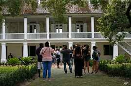 In this July 14, 2017 file photo, visitors walk outside the main plantation house at the Whitney Plantation in Edgard, La. The…