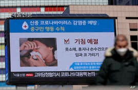 A huge screen about precautions against the COVID-19 is seen in downtown Seoul, South Korea, Sunday, Feb. 23, 2020. South Korea…