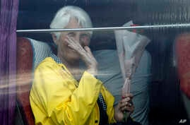 A passenger waves from a bus after she disembarked from the MS Westerdam, owned by Holland America Line, at the port of…