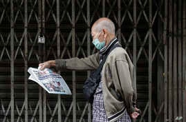 """A man wearing a protective mask reads a Chinese language newspaper that says """"Philippines bans travelers from China, Hong Kong…"""
