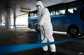 FILE - In this Feb. 1, 2020, file photo, State Commission of Quality Management staff in protective gear disinfects a ground…
