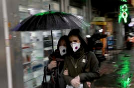 Pedestrians wear masks and gloves to help guard against the Coronavirus in downtown Tehran, Iran, Tuesday, Feb. 25, 2020. The…
