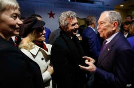 Democratic presidential candidate and former New York City Mayor Michael Bloomberg, right, meets with supporters during a…