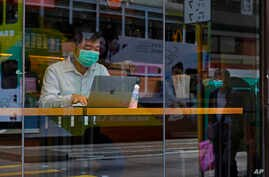 A man wearing a face mask sits at a coffee shop in Hong Kong Saturday, Feb. 22, 2020. COVID-19 viral illness has sickened tens…