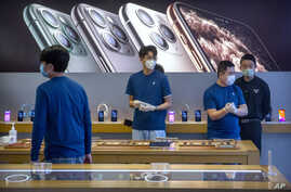 Employees wear face masks as they stand in a reopened Apple Store in Beijing, Friday, Feb. 14, 2020. China on Friday reported…