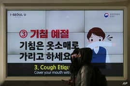 People wearing face masks pass by an electric screen about precautions against the illness COVID-19 in Seoul, South Korea,…