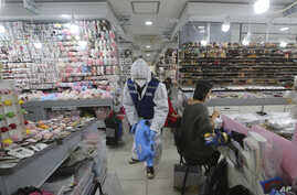 A worker wearing protective gears sprays disinfectant inside a store as a precaution against a new coronavirus at Namdaemun…