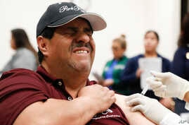 Cesar Gonzalez reacts to getting an influenza vaccine shot at Eastfield College in Mesquite, Texas, Thursday, Jan. 23, 2020…