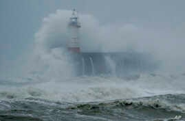 Waves crash over the harbour and a lighthouse, as Storm Ciara hits Newhaven, on the south coast of England, Sunday, Feb. 9,…